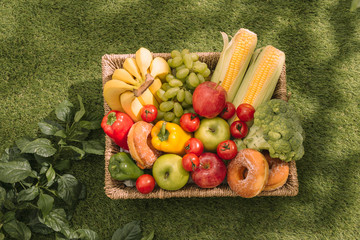 Picnic on the grass. Red checked tablecloth, basket, healthy food sandwich and fruit, orange juice. Top view. Summer Time Rest. Flat lay.