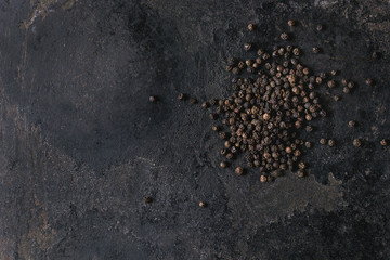 Canvas Prints Spices Heap of black pepper peppercorns over old black iron texture background. Top view, copy space.
