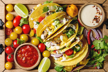 Variety of vegetarian corn tacos with vegetables, green salad, chili pepper served on wooden tray with tomato and cream sauces with ingredients above. Top view, close up.