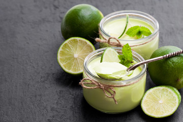 Natural  lime yogurt in a small glass jar on black stone background