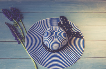 Women's accessories view from above. Conceptual image. Female hat and lupine flowers on a wooden background.
