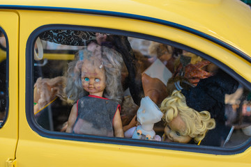 old broken dolls in the car window