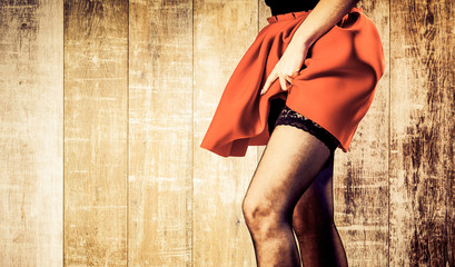 sexy woman legs in red skirt on vintage wooden background