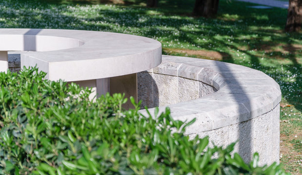 white stone bench in a summer park