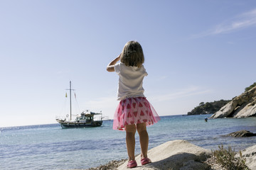 Back view of little girl with binoculars watching boat