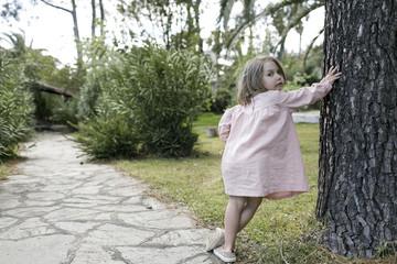 Portrait of little girl leaning against tree trunk in garden