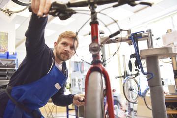 junger Fahrradmechaniker repariert bike in der Werkstatt eines Radladens - einstellen der Scheibenbremse (fahrrad, reparatur,mechaniker,werkstatt,fahrradgeschäft,radladen)