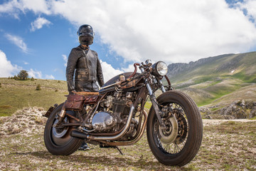 Biker with black leather suit and mask stay with his  custom special rat motorbike in a desolated mountain landscape. Post apocalyptic concept