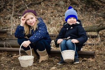 adorable brother and sister siblings sitting outside holding easter baskets for egg hunt