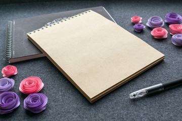 Mockup with empty sketchbook or notebook with brown kraft paper, black pen and paper pink and lilac roses on dark felt background. Cute mock up for elegant design to display your artworks.