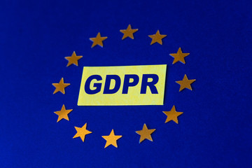 General Data Protection Regulation concept. Letters GDPR on yellow sticker and European Union flag with gold stars on a blue background. Selective focus