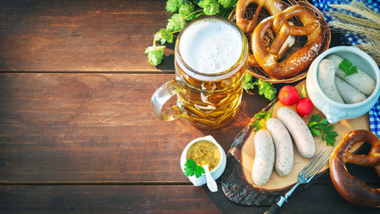 Bavarian sausages with pretzels, sweet mustard and beer mug on rustic wooden table