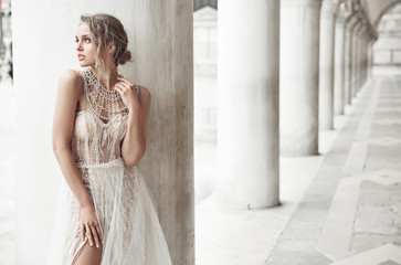 Beautiful bride in long elegant, luxury ivory dress and messy updo hairstyle, posing near columns in Venice, Italy