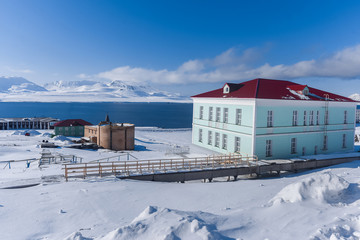 Landscape of the Russian city of Barentsburg on the Spitsbergen archipelago in the winter in the Arctic In sunny weather and blue sky