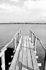 Old wooden bridge or pier to the sea in black and white, Thailand.
