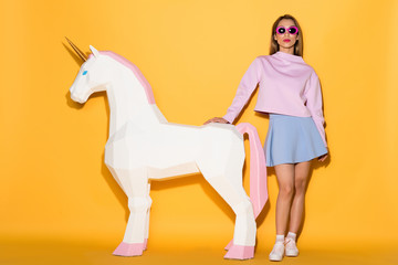 Aluminium Prints Wild West stylish asian female model in sunglasses and decorative unicorn on yellow background