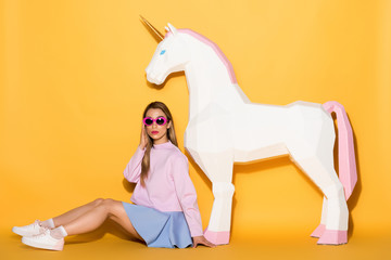 decorative unicorn and stylish asian female model in sunglasses sitting on floor on yellow background