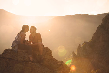 Young couple at mountains on the sunset