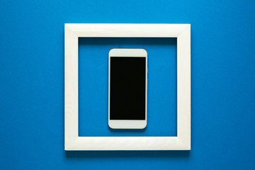Minimalism. Masterpiece in wooden frame. Smartphone with headphones. Top view. Flat lay. Technology as art concept.