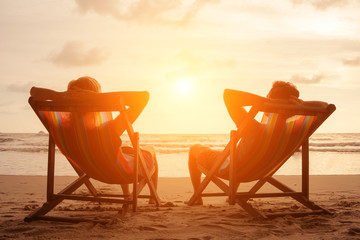 Romantic holiday travel. Silhouette of happy young couple sitting in deck chairs in luxury beach hotel at sunset near the sea. Love and relationship concept. Summer vacation in tropical paradise islan