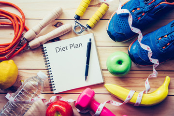 Workout ideas with exercise equipment and notebooks for weight loss programs on wooden floors.