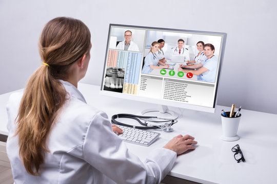 Doctor Video Conferencing With Colleagues On Computer