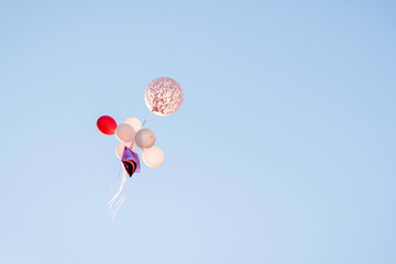 Bunch of trendy colorful balloons in blue sky.