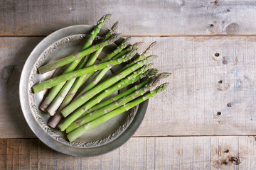 Banches of fresh green asparagus in a metallic jar on wooden background