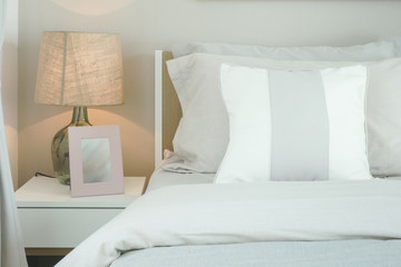 Close up pillows on bed with reading lamp and picture frame