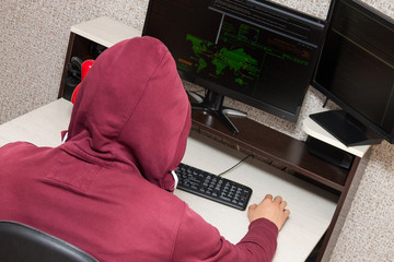 Hacker using his computer at home. Man in a red hoodie breaks the access to steal information and infects computers and systems