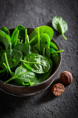 Healthy green spinach on gray old stone