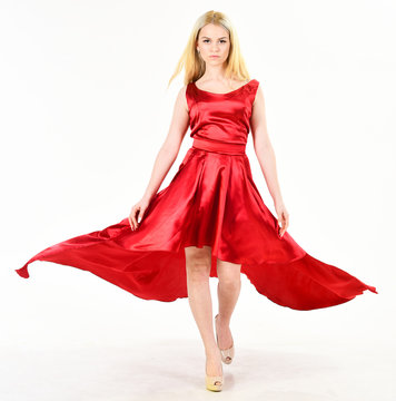 Dress rent service, fashion industry. Woman wears elegant evening red dress, white background. Lady rented fashionable dress for visiting event. Dress rent concept. Girl blonde posing in dress.