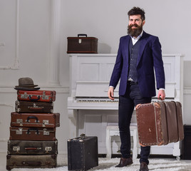 Macho elegant on smiling face stands near pile of vintage suitcase, holds suitcase. Man, traveller with beard and mustache with luggage, luxury white interior background. Baggage delivery concept.