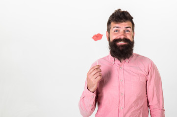 Photo booth fun concept. Man holding paper party props lips, white background. Hipster with beard and mustache on cheerful face posing with photo booth props, copy space