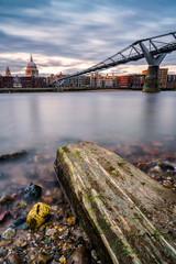 St. Paul's Cathedral and the Millenium Bridge seen from the river bank with the Thames at low tide