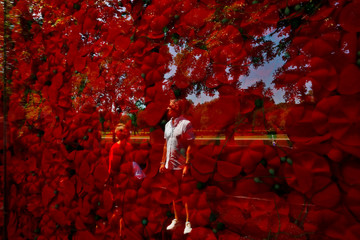A man is seen reflected on a temporary memorial made of over 600,000 poppies ahead of Memorial Day at the National Mall in Washington, U.S.