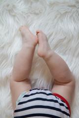 Baby legs on white fur