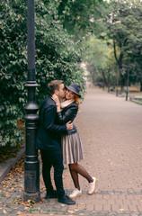 Happy couple in love walking in the green park. Man kissing blonde woman near the lantern.