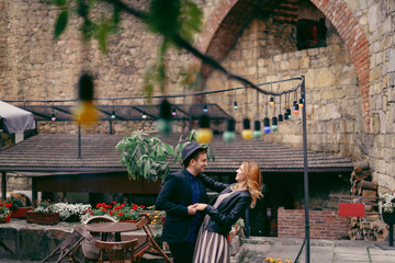 Happy smiling couple in casual clothes dancing on the terrace of the old cafe outdoors. Castle wall background. Old city in Europe