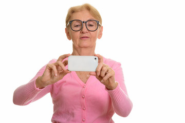 Senior nerd woman taking picture with mobile phone
