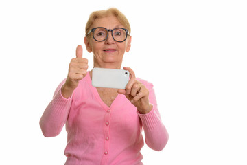 Happy senior nerd woman smiling while taking picture with mobile