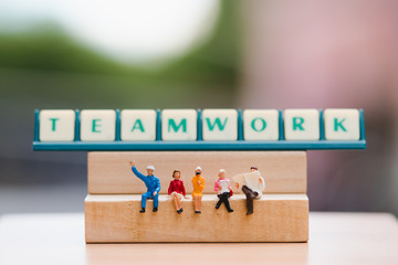 Miniature people sitting on wooden block and teamwork words background using as education and business concept