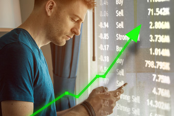 Man on mobile device for trading and stock market upward trend.  Increase value with green arrow and chart overlay.  Ticker with current trading prices.