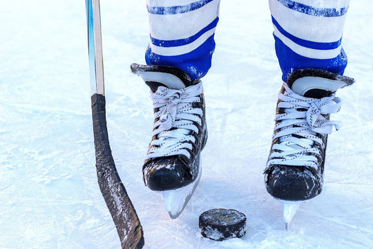 legs young hockey player, hockey stick and puck close-up on the background of  ice.