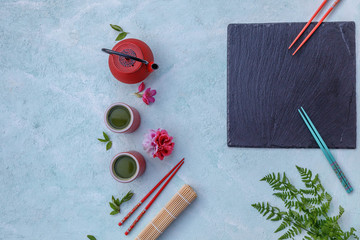 Asian food background, red tea pot, caps and chopsticks on blue concrete background. Top view, flat lay