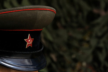 Shallow depth of field. A symbol of a Soviet soldier: a cap with a five-pointed star. Officer of the USSR during the Great Patriotic War. Green background with copy space.
