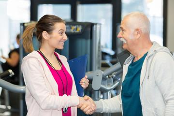 female coach meeting senior man client at the gym club