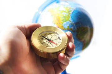 compass in man's hand with the globe on the background . travel and explore concept
