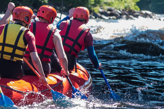 Rafting in life jackets, men row oars on a catamaran. Extreme sports in a mountain river