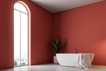 Minimalistic red bathroom corner, white bathtub
